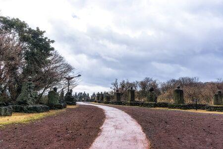 array of grandfather stones in jeju stone park, south korea