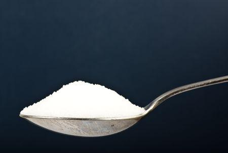 sugar on spoon on dark background
