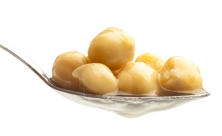 chickpeas on metal spoon on white background