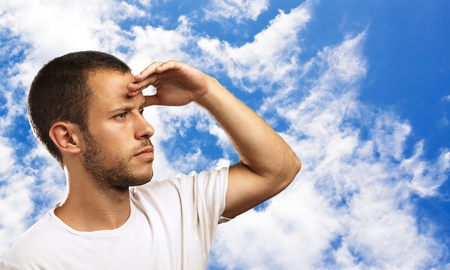 young man looking forward to the future on a blue sky background