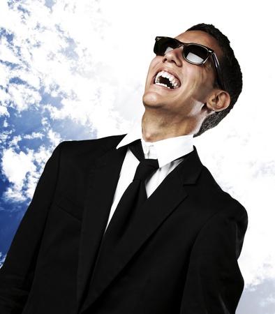 Foto de portrait of young man laughing in suit and sunglasses against a blue sky background - Imagen libre de derechos