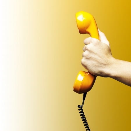 Hand holding vintage telephone receiver isolated over yellow background
