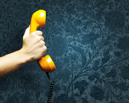 hand holding a vintage telephone against a grunge background
