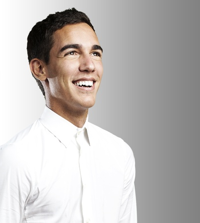 portrait of young man with white shirt smiling against a grey background