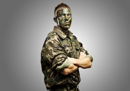 portrait of young soldier with jungle camouflage paint on a grey background
