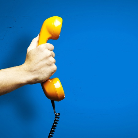 Photo pour Hand holding vintage telephone receiver isolated over blue background - image libre de droit