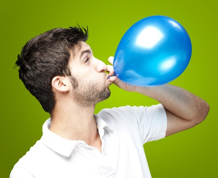 portrait of young man blowing a balloon over green background