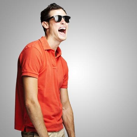 Foto de portrait of young man with sunglasses laughing over grey background - Imagen libre de derechos