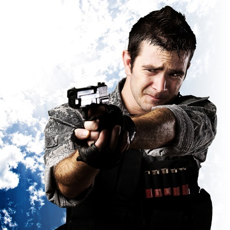 portrait of scared soldier aiming with gun against a cloudy sky background