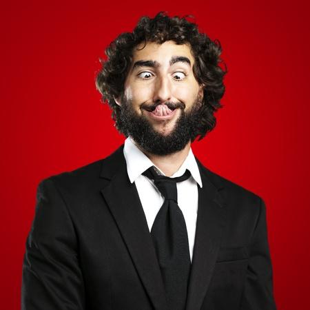 Photo pour portrait of young business man showing the tongue over red background - image libre de droit