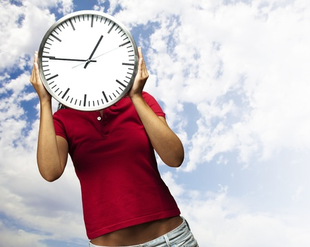 woman holding clock in front of head against a cloudy sky background