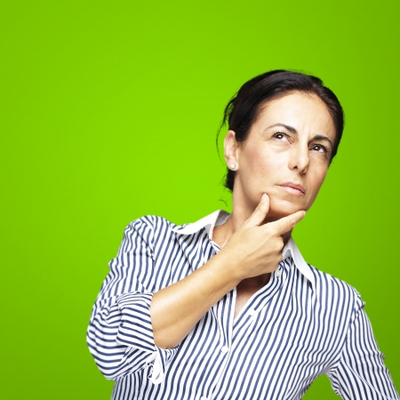 portrait of a middle aged woman thinking against a green backgroundの写真素材