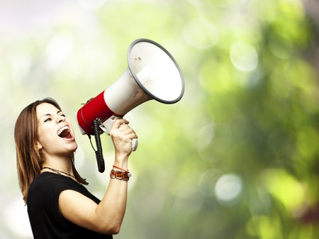 portrait of middle aged woman shouting using megaphone against a nature background