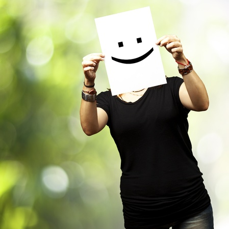 Photo for Woman showing a blank paper with a smile emoticon in front of her face against a nature background - Royalty Free Image