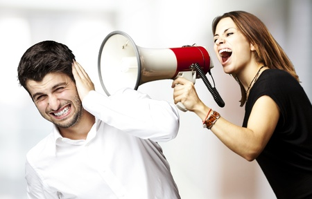 young woman screaming a man with the megaphone against a abstract backgroundの写真素材
