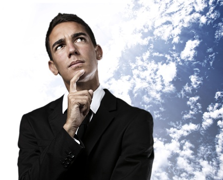 portrait of business man thinking against a cloudy sky background