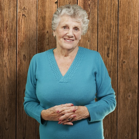 portrait of senior woman standing against a wooden wall