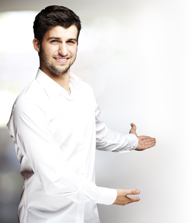 portrait of a handsome young man gesturing welcome indoor