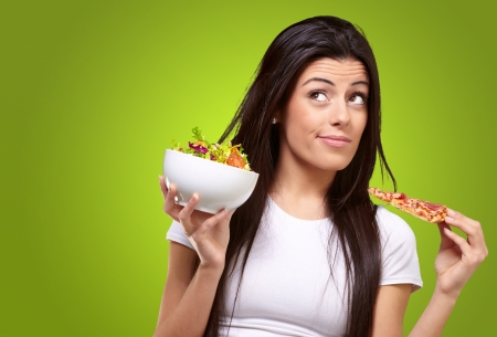 portrait of young woman choosing pizza or salad against a green background