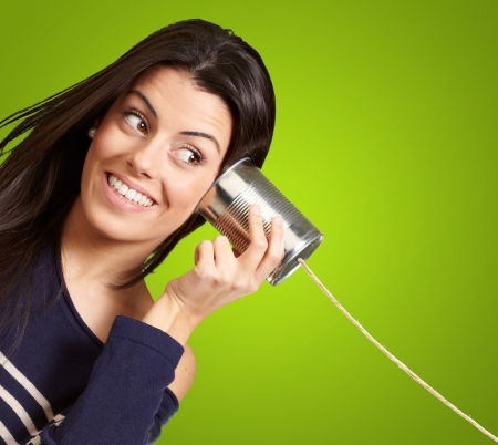 Photo for Young woman hearing using a metal tin can over green background - Royalty Free Image