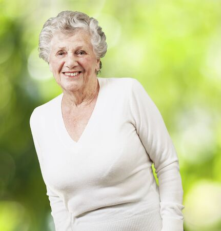 Photo for pretty senior woman smiling against a nature background - Royalty Free Image