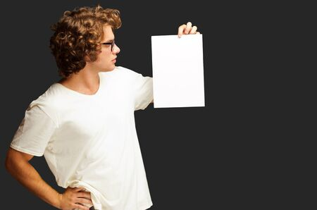 Portrait Of Man Holding A Blank Paper Isolated On Black Background