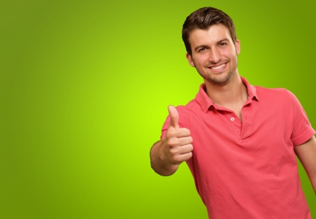 young man smiling with thumbs up isolated on green background