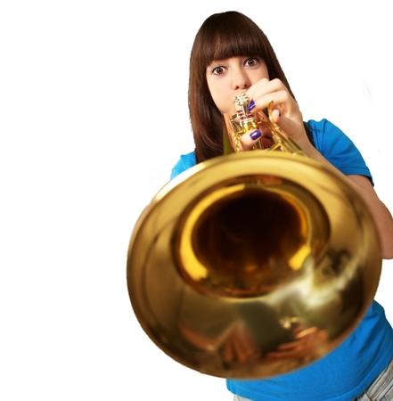 Photo pour portrait of a young girl blowing trumpet on white background - image libre de droit