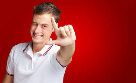 Portrait Of A Handsome Young Man Gesturing On Red Background