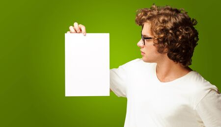 Portrait Of Man Holding A Blank Paper Isolated On Green Background