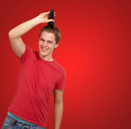 portrait of young man cutting his hair over red background