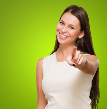 Portrait Of A Happy Young Woman Pointing At You against a green background