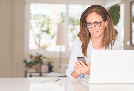 Photo pour Middle age woman using smartphone and laptop, indoor - image libre de droit