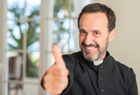 Photo pour Christian priest man happy with big smile doing ok sign, thumb up with fingers, excellent sign - image libre de droit