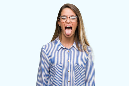 Photo pour Beautiful young woman wearing elegant shirt and glasses sticking tongue out happy with funny expression. Emotion concept. - image libre de droit