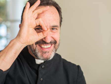 Christian priest man with happy face smiling doing ok sign with hand on eye looking through fingers