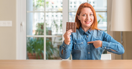 Redhead woman holding chocolate bar at home with surprise face pointing finger to himself