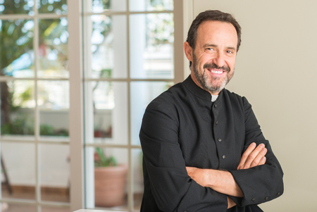 Photo pour Christian priest man with a happy face standing and smiling with a confident smile showing teeth - image libre de droit