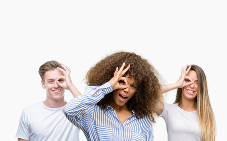 Group of young people over white background with happy face smiling doing ok sign with hand on eye looking through fingers
