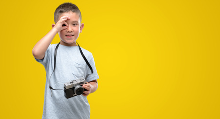 Dark haired little child holding vintage camera with happy face smiling doing ok sign with hand on eye looking through fingers