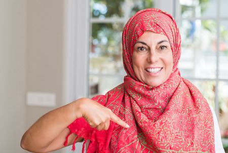 Middle aged muslim woman wearing hijab with surprise face pointing finger to himself