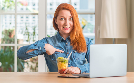 Redhead woman using computer laptop eating fruit at home with surprise face pointing finger to himself