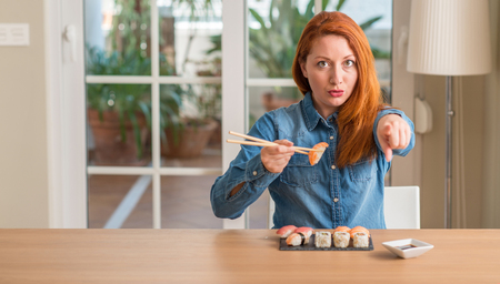 Redhead woman eating sushi using chopsticks pointing with finger to the camera and to you, hand sign, positive and confident gesture from the front