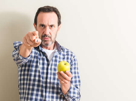 Senior man holding a green apple pointing with finger to the camera and to you, hand sign, positive and confident gesture from the front
