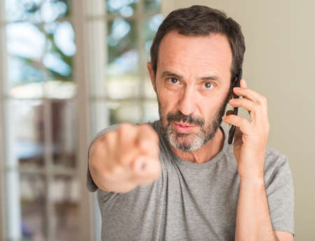 Middle age man using smartphone pointing with finger to the camera and to you, hand sign, positive and confident gesture from the front