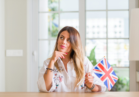 Young woman at home holding flag of United Kingdom serious face thinking about question, very confused idea