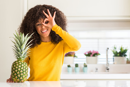 African american woman and pineapple tropical fruit with happy face smiling doing ok sign with hand on eye looking through fingers