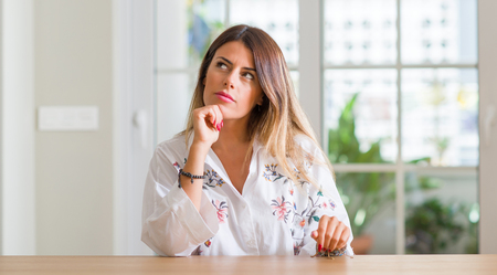 Young woman at home serious face thinking about question, very confused idea