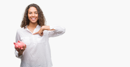 Young hispanic woman holding piggy bank with surprise face pointing finger to himself