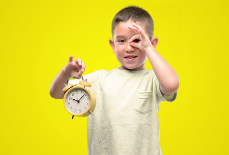 Little child holding alarm clock with happy face smiling doing ok sign with hand on eye looking through fingers